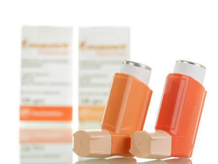 Foto de Two of the asthma inhaler and packaging of medicines isolated on white background. - Imagen libre de derechos