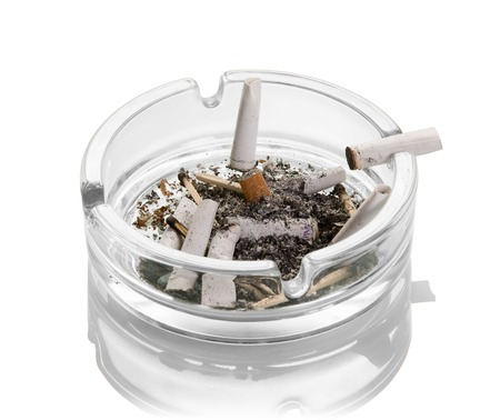Photo for Cigarette butts, ashes, burnt matches in a glass ashtray isolated on white background. Close-up - Royalty Free Image