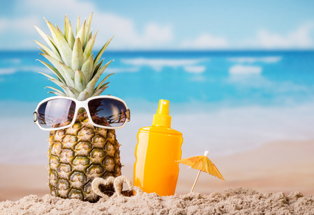 Photo pour Pineapple with sunglasses, umbrella and sunscreen, on beach - image libre de droit