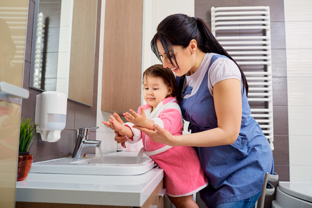 Foto de Mother and daughter washing their hands in the bathroom. Care and concern for children. - Imagen libre de derechos