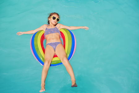 Photo for A teenage girl in a circle ring in the water at the pool. - Royalty Free Image