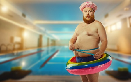 Photo for Fat funny man in the inflatable circle in the pool. - Royalty Free Image