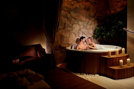 Photo pour A loving couple with a glass of champagne in a jacuzzi with candles relax. - image libre de droit