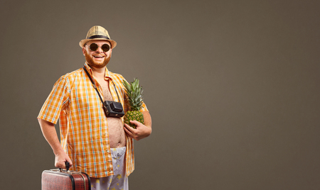 Photo pour A funny fat bearded tourist with a pineapple and a suitcase smiles against the background for the text. - image libre de droit