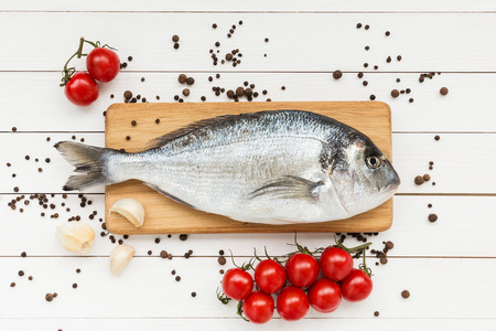 Foto de Fresh dorado fish on wooden cutting board with tomatoes - Imagen libre de derechos