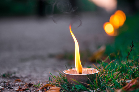 Photo for Macro shot of lit candle burning with soft glowing flame and smoke on evening background. Candle path at the park close to the seaside during the Night of ancient lights - Royalty Free Image