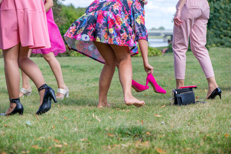 Photo pour Girls wearing off high heel shoes in grass. Cheerful bride and bridesmaids party before wedding. Women having fun. Ladies purse, pink high heel shoes, smart phone left in grass. Girls freedom concept - image libre de droit