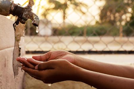 Foto de Closeup of hands, child drinking water directly from corporation tap water in India. - Imagen libre de derechos