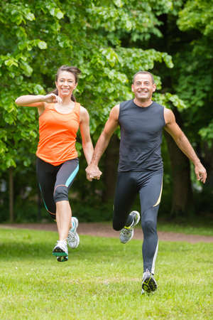 Sport couple in front of green forest