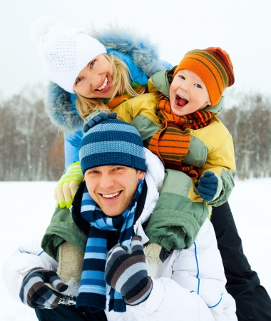 happy family, young couple and their son spending time outdoor in winter
