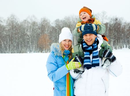 happy young family spending time outdoor in winter park