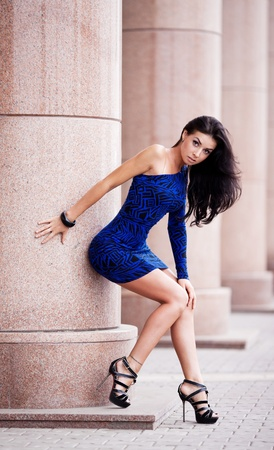 very beautiful young brunete woman wearing a blue mini dress in the street