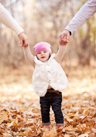 Photo for happy family with their baby spending time outdoor in the autumn park  and teaching her walking - Royalty Free Image