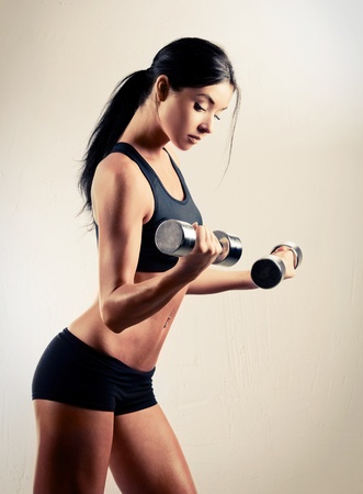 studio portrait of a beautiful sporty muscular woman working out with two dumbbells