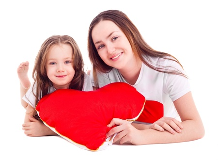 happy mother and her six year old daughter with a heart-shaped pillow, isolated against white background