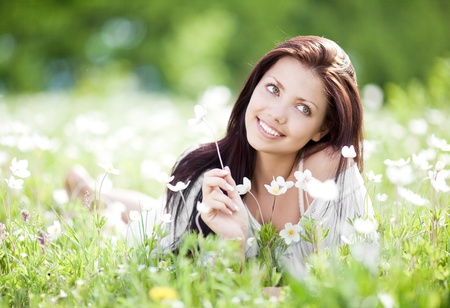 beautiful young brunette woman relaxing on the  meadow with white flowers  on a warm summer day