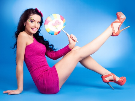 pretty young brunette woman with a lollipop, isolated against blue background