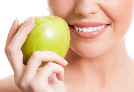 closeup of the face of a woman holding a green apple, isolated against white background