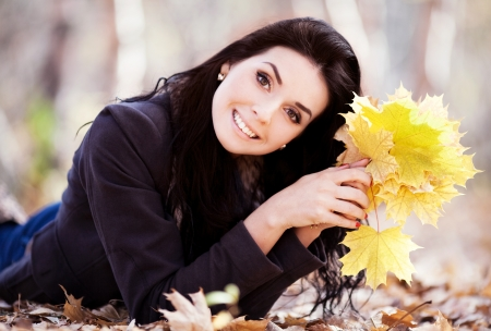 beautiful woman with yellow leaves in the autumn park