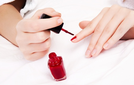 hands of a woman applying red nail polish