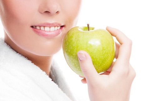 closeup of the face, hands and healthy white teeth of a woman holding an apple, isolated against white background