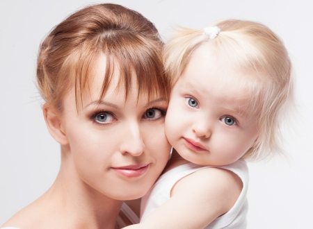 young mother with her baby, on white studio background