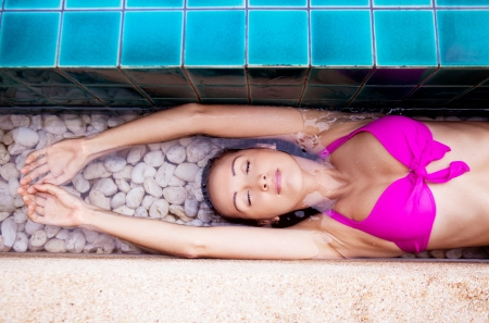 beautiful young brunette woman relaxing in the swimming pool
