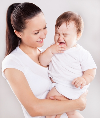 beautiful young mother holding a crying baby, against light studio background