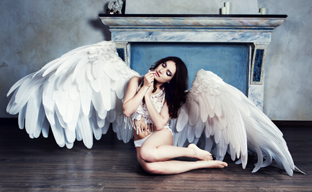 Photo for beautiful sad young model with angel wings in the studio - Royalty Free Image