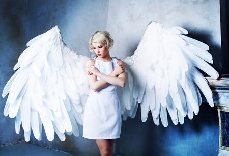 Foto de beautiful young model wearing a white dress with angel wings in the studio - Imagen libre de derechos