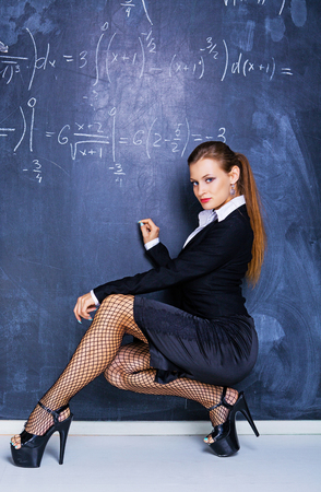 Photo for attractive striptease dancer dressed as teacher against a chalkboard in the classroom - Royalty Free Image