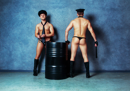 Photo for striptease dancers wearing costumes of policemen in the studio - Royalty Free Image