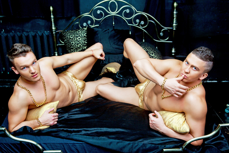 Photo for two attractive muscular men wearing  golden chains and underwear   in bed with black linen - Royalty Free Image