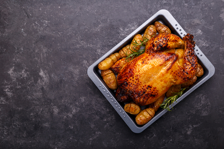 Photo for Roasted chicken and potatoes on black slate stone background, flat lay with copy space. Menu or recipe template - Royalty Free Image