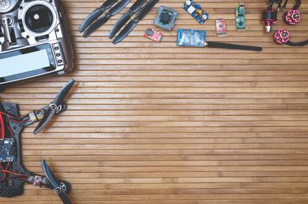 Foto de Assembly drone accessories quadcopter on a wooden background, space for ads and inscriptions - Imagen libre de derechos