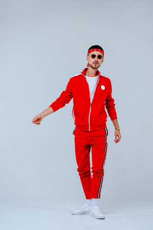 Foto per health, fun, people sport concept - happy young man wearing red sport suit on white background. - Immagine Royalty Free
