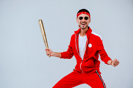 Foto per cheerful fashionable man wearing a red sports suit in his hand a gold baseball bat is more than a little surprised. proud and successful. - Immagine Royalty Free