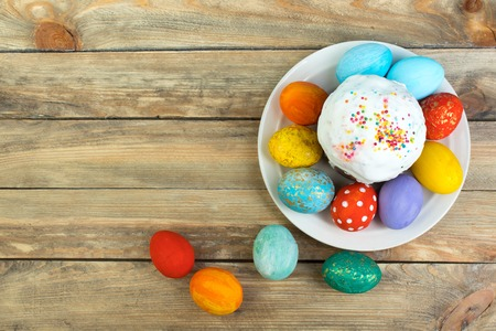 Photo for Happy Easter card. Colorful shiny easter eggs cake with white icing and sugar decor on the table decorated in rustic style. Copy space for text. - Royalty Free Image