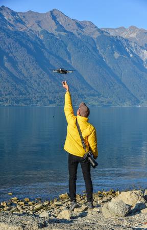 Foto de A young man traveler using a drone to take photos of Lake Brienz, Switzerland. - Imagen libre de derechos