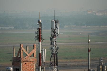 Foto de Saigon, Vietnam - Jan 6, 2019. Telephone antenna on roof top of building in polluted air. - Imagen libre de derechos