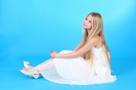 Photo pour pretty teenage blond girl in the white dress over the blue background - image libre de droit