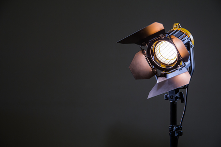 Foto per Floodlight with halogen lamp and Fresnel lens on a gray background. Lighting equipment for shooting. Filming and photographing in the interior. - Immagine Royalty Free