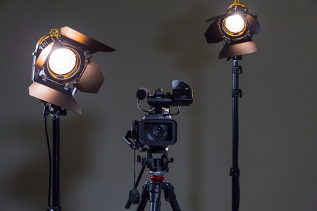 Foto per Camcorder and 2 spotlights with Fresnel lenses in the interior. Shooting an interview. - Immagine Royalty Free