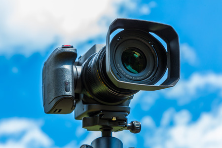 Photo for Digital camera closeup on a background of sky and clouds. Shooting on location and nature. - Royalty Free Image