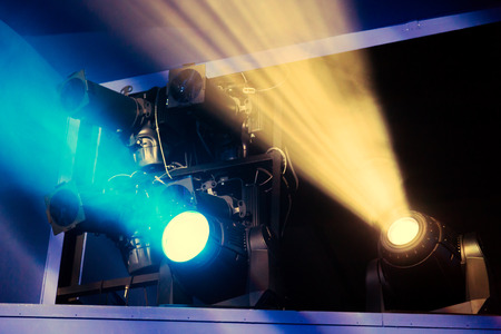 Foto de Lighting equipment on the stage during the performance. The light from the spotlight through the smoke. Blue and yellow rays of light. - Imagen libre de derechos