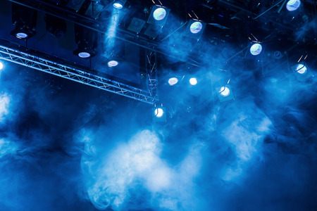Foto de Blue light rays from the spotlight through the smoke at the theater or concert hall. Lighting equipment for a performance or show. - Imagen libre de derechos