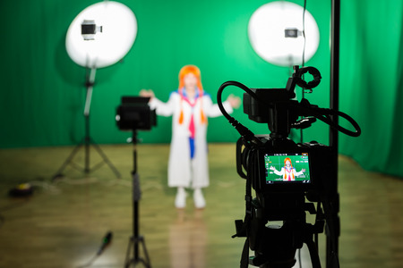 Photo for Actress in theatrical costume in a Television Studio. Green screen and chroma key. Lighting equipment and filming equipment. - Royalty Free Image