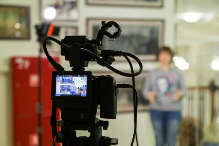 Foto de TV shooting at the Museum. LCD monitor on the camcorder. The girl in front of the camera. A record of the interview. Filming equipment and lighting equipment. - Imagen libre de derechos