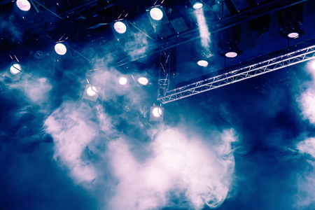 Foto per Blue light rays from the spotlight through the smoke at the theater or concert hall. Lighting equipment for a performance or show - Immagine Royalty Free