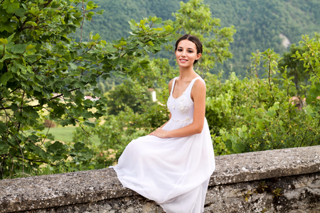 Photo pour beautiful young woman sitting on a stone wall in romantic white dress in the nature - image libre de droit